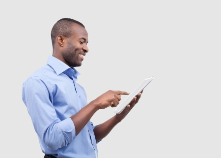 Working on digital tablet. Side view of handsome African man working on digital tablet and smiling while standing isolated on grey photo