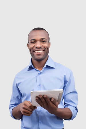 Working on digital tablet. Front view of handsome African man working on digital tablet and smiling at camera while standing isolated on grey Stock Photo