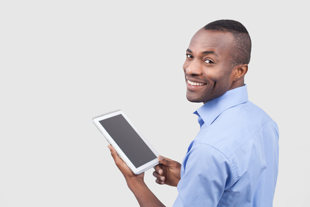 over the shoulder view: Working on digital tablet. Rear view of young African man working on digital tablet and looking over shoulder while standing isolated on grey Stock Photo