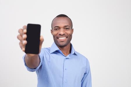 te negro: Es para usted. Hombre negro alegre estirando un teléfono móvil y sonriendo mientras está de pie aislado en gris