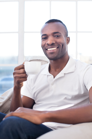 Man drinking coffee. Cheerful African man drinking coffee and smiling photo