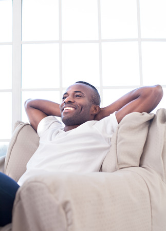 african ethnicity: Relaxing at home. Cheerful African man holding head in hands and smiling while sitting on the chair