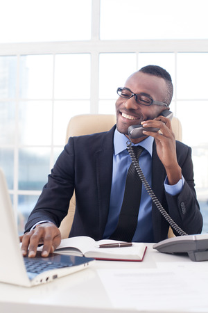 Businessman at work. Confident young African businessman in glasses talking on the mobile phone and using computer while sitting at his working place photo