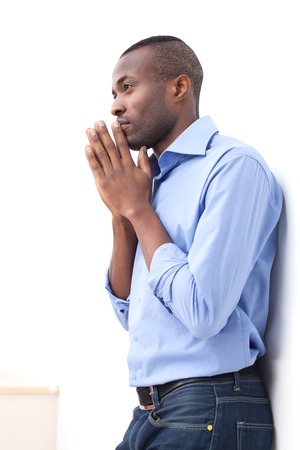 chin on hands: Waiting for inspiration. Side view of handsome young black man keeping his hands clasped and looking away while leaning at the wall