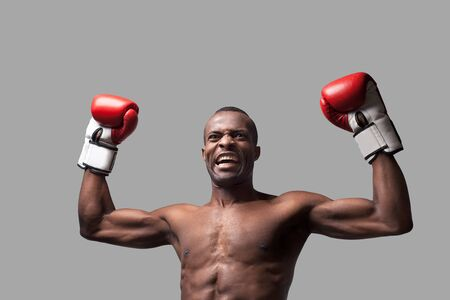 I am the best! Young African boxer raising his hands up and grimacing while standing isolated on grey photo