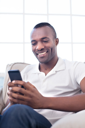 Man with mobile phone. Cheerful African man typing something on the mobile phone and smiling while sitting on the chair