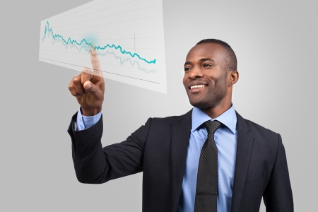 Innovative business. Cheerful young African man in formalwear pointing diagram on the transparent wipe board while standing against grey background photo