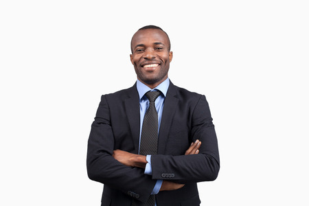 Confident businessman. Cheerful young African man in formalwear keeping arms crossed and smiling at camera while standing against white background