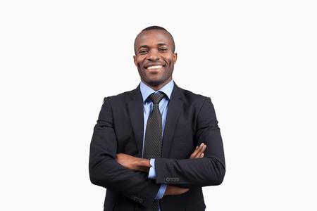 Hombre de negocios confidente. Hombre africano joven alegre en ropa formal manteniendo los brazos cruzados y sonriendo a la cámara mientras está de pie contra el fondo blanco Foto de archivo - 24397568