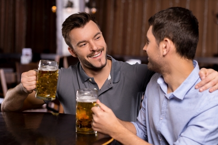 jovenes tomando alcohol: Relajarse en cervecería. Dos hombres jóvenes alegres que beben la cerveza en barra Foto de archivo