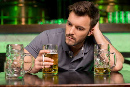 Lonely man in bar. Depressed young man drinking beer and holding hand in hair while sitting in bar  photo
