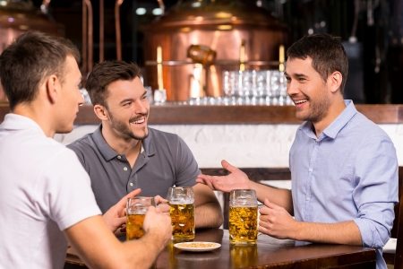 bar counter: Spending time in bar. Three cheerful friends drinking beer in bar