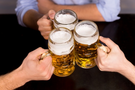 beer mug: Cheers! Close-up top view of people holding mugs with beer Stock Photo