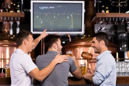 Kijken naar een voetbalwedstrijd. Achter mening van drie gelukkige mannen kijken naar een voetbalwedstrijd en gebaren tijdens de vergadering in bar Stockfoto