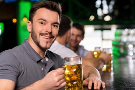 hombre tomando cerveza: El hombre en el bar. Apuesto joven bebiendo cerveza en el bar y sonriendo Foto de archivo