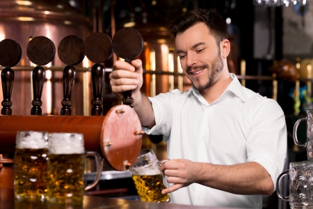 beer in bar: Freshly tapped beer. Cheerful young bartender pouring beer and smiling