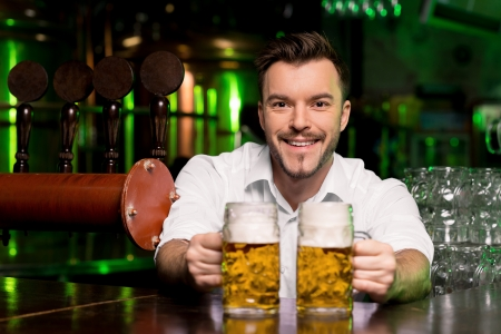 Freshly tapped beer. Handsome smiley bartender stretching out beer mugs and smiling Stock Photo