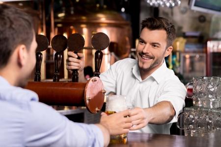 Hier is je bier. Vrolijke jonge barman die een mok met bier naar de klant Stockfoto