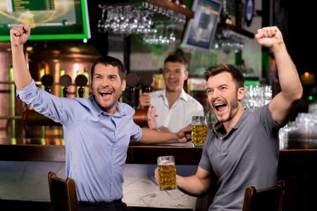 handle bars: Ver la televisi�n en el bar. Dos j�venes felices bebiendo cerveza y haciendo gestos mientras se est� sentado en la barra Foto de archivo