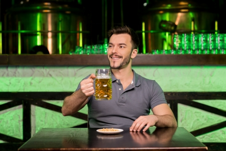 handle bars: What a great day! Cheerful young man holding a mug with beer and smiling while sitting in bar