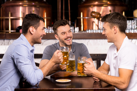 Spending time in bar. Three cheerful friends drinking beer in bar photo