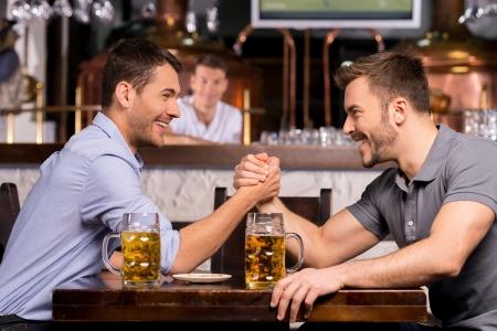 handle bars: Viejos amigos. Dos hombres j�venes alegres bebiendo cerveza y divirti�ndose en la barra de