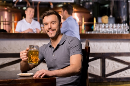 handle bars: Man in beer pub. Cheerful young man holding a beer mug and smiling while sitting in bar Stock Photo