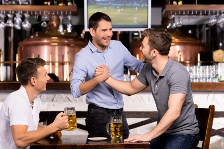 Old friends meeting. Three cheerful friends meet each other in beer pub photo