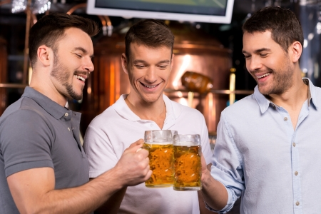 Old friends meeting. Three cheerful young men drinking beer in bar photo