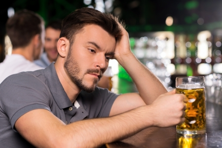 It was a hard day. Depressed young man drinking beer in bar and holding hand in hair