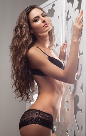 Confident in her beauty. Attractive young woman in black lingerie posing and looking at camera photo