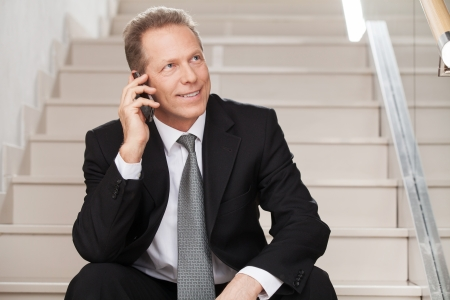 He is always in touch. Cheerful mature man in formalwear talking on the mobile phone and smiling while sitting on staircase  photo