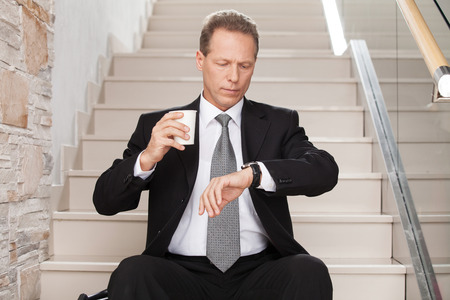 Late again. Worried mature man in formalwear holding a coffee cup and checking a time while sitting on staircase  photo