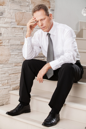 mature businessman: Depressed businessman. Depressed mature man in formalwear holding head in hand while sitting on staircase