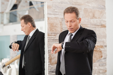 checking the time: Late again. Worried mature man in formalwear checking a time