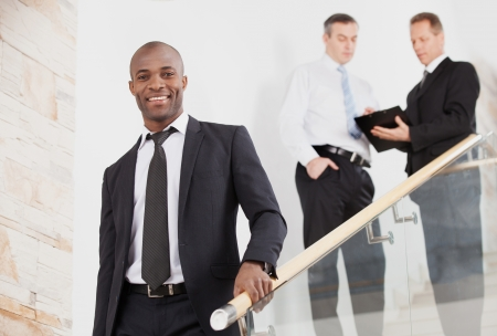 moving down: Confident businessman. Cheerful young black man in formalwear moving down by staircase and smiling while two people talking on background