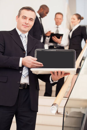 Businessman with laptop. Cheerful mature man in formalwear standing on staircase and pointing laptop while three people talking on background photo