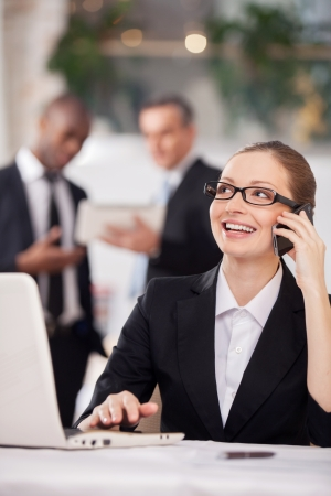 Businesswoman on the phone. Cheerful young woman in formalwear sitting at the table and talking on the mobile phone while two colleagues standing on background photo