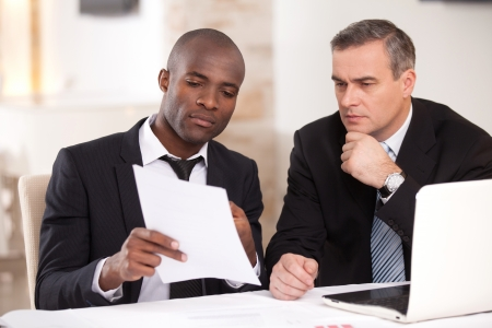 discussing: Discussing a project. Two confident business people in formalwear discussing something while one of them pointing a paper