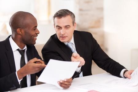 dos personas hablando: Contrato en buenas condiciones. Dos hombres de negocios alegres en ropa formal hablando de algo y que señalan un papel