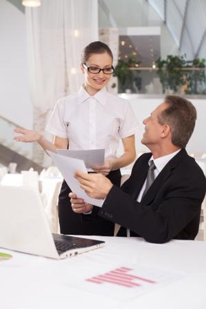 buen trato: Fue un buen negocio. Hombre alegre en ropa formal que sostiene un papel mientras que la mujer en camisa blanca de pie cerca de �l y haciendo gestos Foto de archivo