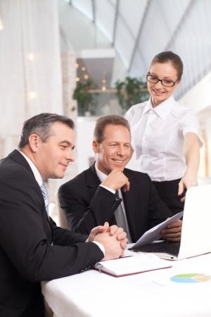buen trato: Fue un buen negocio. Dos hombres alegres en ropa formal que se sientan en la mesa mientras que la mujer en camisa blanca de pie cerca de ellos y se�alando monitor de la computadora