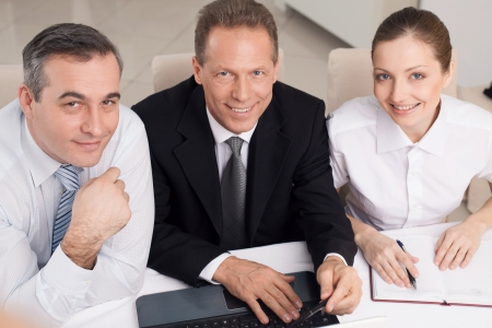 Business people at work. Top view of three cheerful business people in formalwear sitting at the table and looking at camera photo