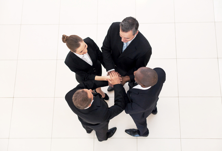 we the people: We are team. Top view of four business people in formalwear standing close to each other and holding hands together
