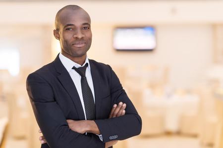 lazo negro: La confianza y carisma. Hombre africano joven alegre en traje completo manteniendo los brazos cruzados y mirando a la c�mara