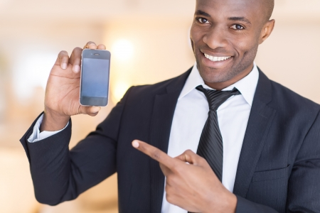 phone: Businessman with mobile phone. Cheerful young African man in formalwear holding a mobile phone and pointing it Stock Photo