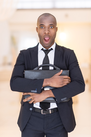 Frustrated businessman. Shocked young African man in full suit holding a bag in his hands and keeping mouth open while looking at camera photo