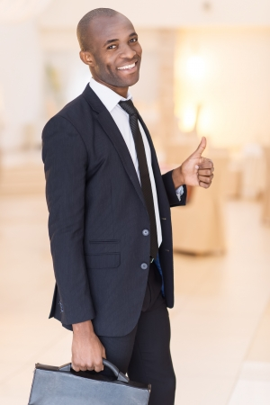 thumbs up symbol: Successful businessman. Cheerful young African man in formalwear holding a briefcase and gesturing while smiling at camera