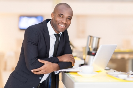 african man: Business on the go. Cheerful young African man in formalwear using his laptop while leaning at bar