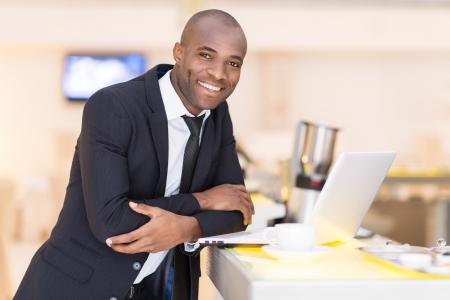 hombres de negro: Negocios sobre la marcha. Hombre africano joven alegre en ropa formal con su ordenador portátil, mientras que apoyado en la barra